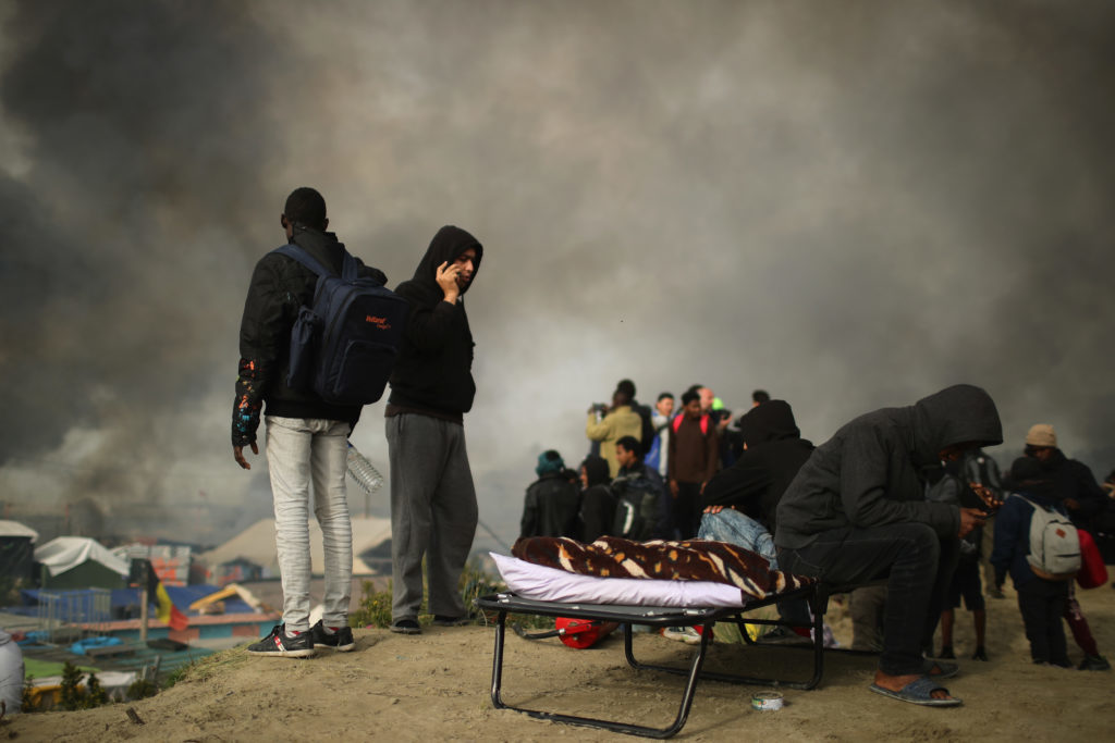 Migrants leave the Jungle camp as fires rage across the notorious camp