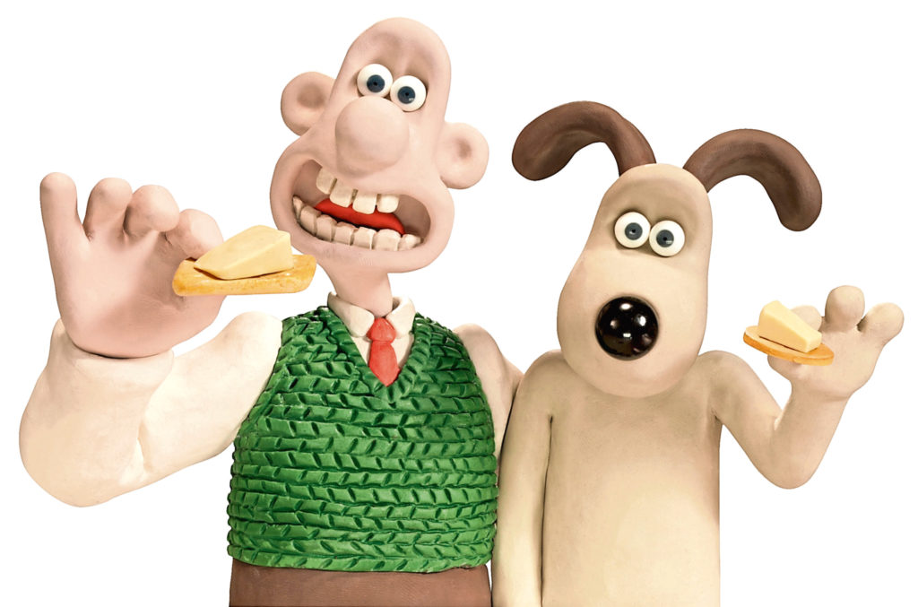 A picture of Wallace and Gromit about to eat cheese on crackers.